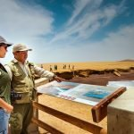 Woman and man look over intrepretation board in desert-like coast