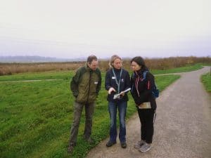 Two western and one Chinese person on a grey wetland