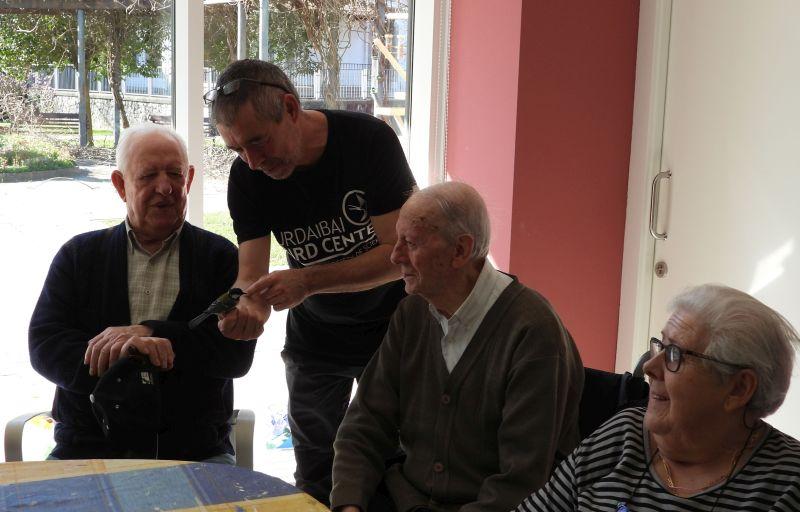 A man shows a bird to three senior citizens