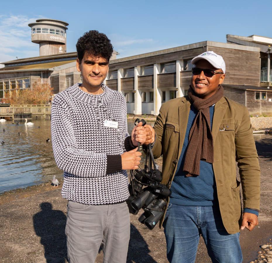 Adil hands many binoculars to Ibrahim