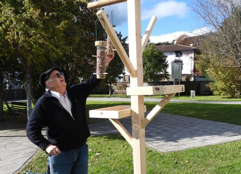 An older man with walking stick hangs up a bird feeder