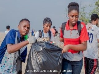 Young people haul full trash bag