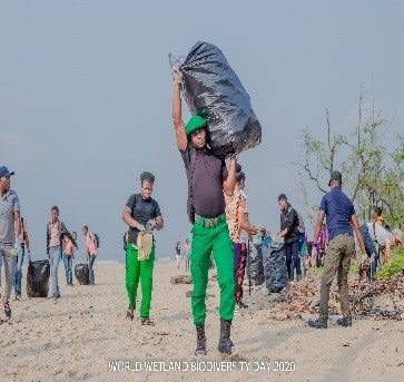 Man in uniform hauls a bag of trash on his shoulder