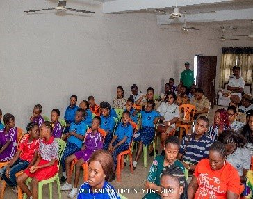 Children and adults sit listening in rows