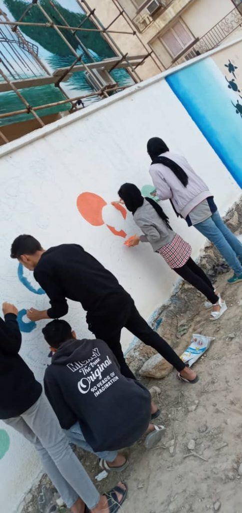 Young people paint building hoardings