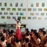 Girls points to wetland species photos on wall