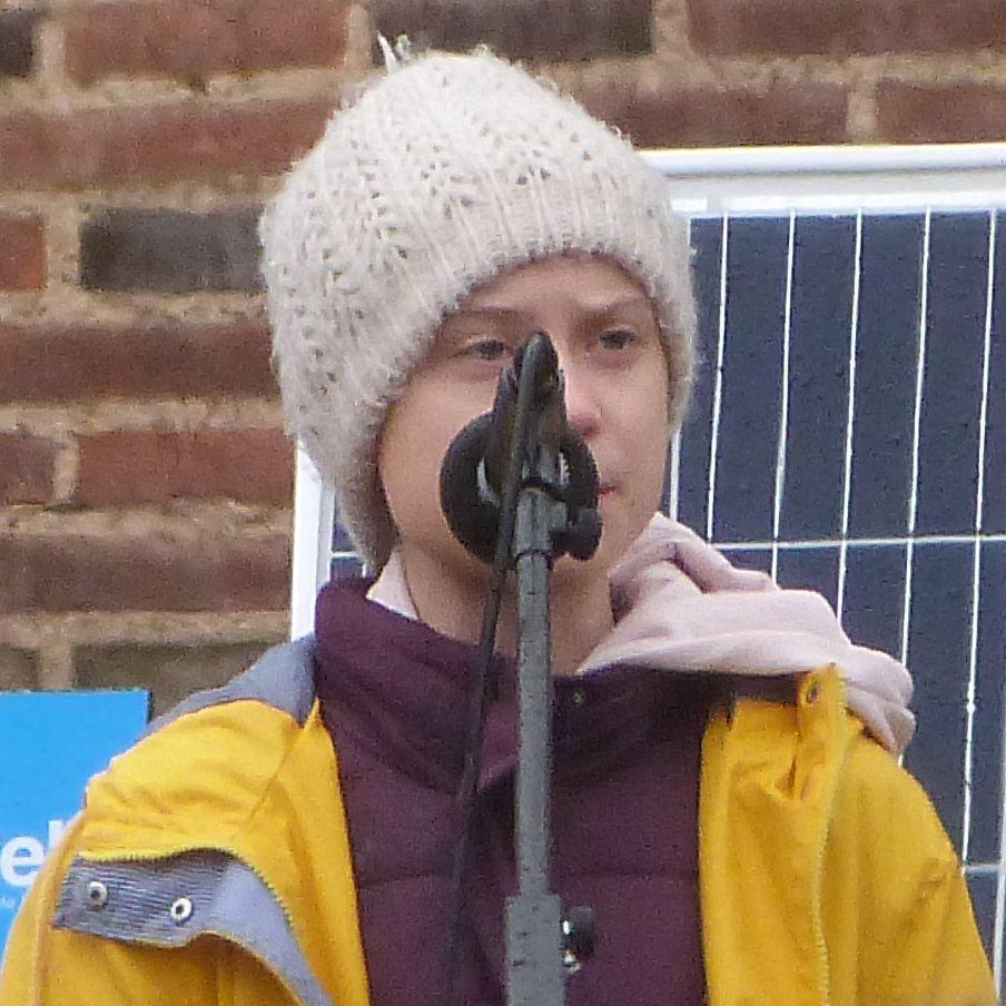 Greta Thunberg speaking to crowd, in yellow raincoat