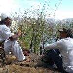 Two men sitting by lake