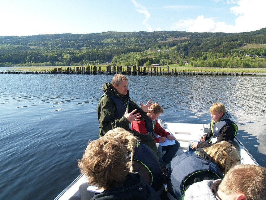 Guide talks to kids in boat about lake wall