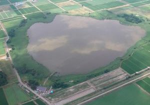 Aerial view of big wetland and small building