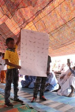 Two children hold upa  hge sheet illustrating different birds, as they stand under canvas